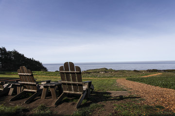 Picturesque ocean view from Adirondack chairs along California's Pacific coast.