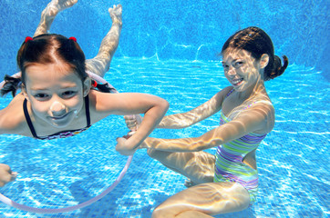 Happy children swim in pool underwater, girls swimming