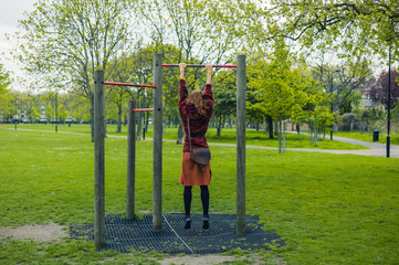 Woman doing pull ups in a park