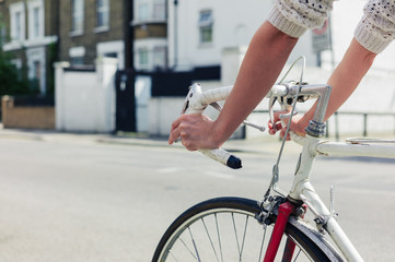 Young woman cycling on a road in the city