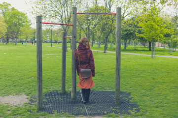 Woman in park by pull up bars