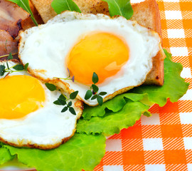 Bacon with sunny side up eggs served with toasts