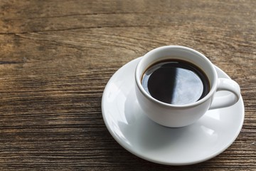 A cup of black coffee on wooden