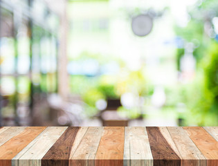 Empty tropical wood table and blurred garden cafe light backgrou
