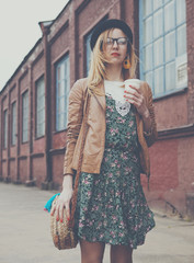 Stylish woman in the street drinking morning coffee.