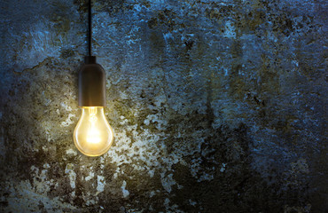 warm light bulb lamp on grunge wall background in the night