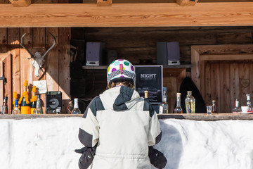 Rear view of woman skiers waiting at mountain lodge counter for