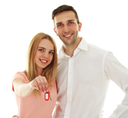 Attractive young couple showing new house key, isolated on white