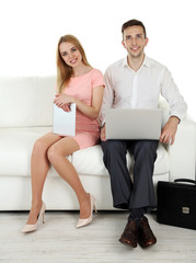 Portrait of young happy couple with baggage, digital tablet and laptop sitting on sofa. Isolated on white