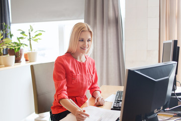 happy creative female office worker with computers