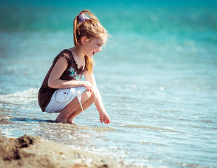 little girl walks on the  beach
