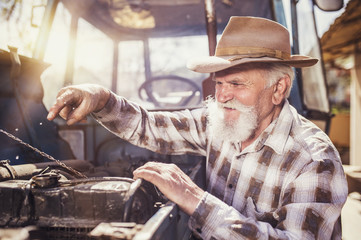 Senior man at the farm repairing an old tractor
