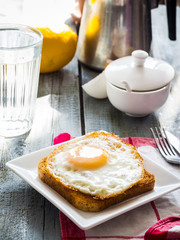 crispy toast with a fried egg and a glass of water, lemon, break