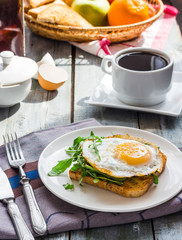 crispy toast with a fried egg and green arugula, coffee cup, fru