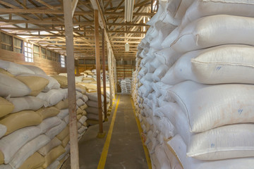 Stack of bags with coffee beans at warehouse
