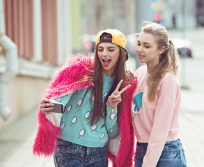 Hipster girlfriends taking a selfie in urban city context -
