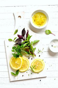 fresh garden herbs and lemon on a white surface