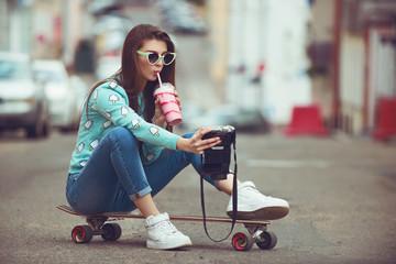 Beautiful young woman posing with a skateboard, fashion