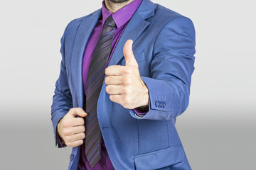 Man in blue suit holding his thumb up