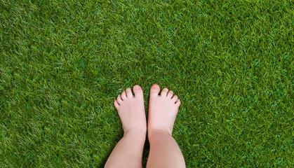 Baby legs standing  on green grass