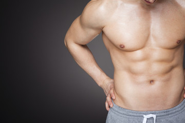 Image of a fit man showing six pack abs against grey background