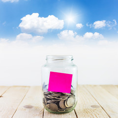Coins in a glass jar with sticky note against blue sky backgroun