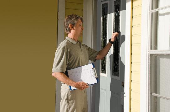 Man doing questionnaire survey or petition work door-to-door