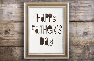 Picture frame with Happy fathers day sign on wooden backround.