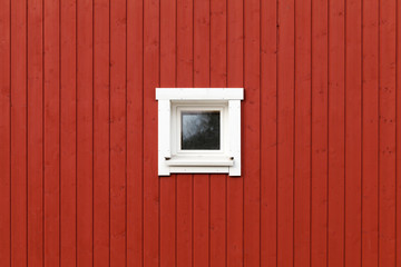 Red wooden wall with small window in white frame