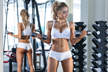 Sexy woman doing exercise with dumbbells