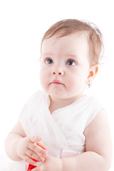 The girl is one year in dress sitting on a white background.
