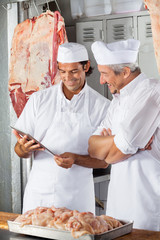 Butchers Looking At Tablet Computer In Butchery
