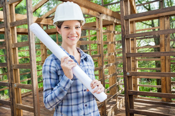 Smiling Engineer Holding Blueprint In Wooden Cabin