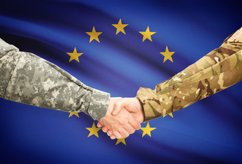 Men in uniform shaking hands with flag on background - Europe
