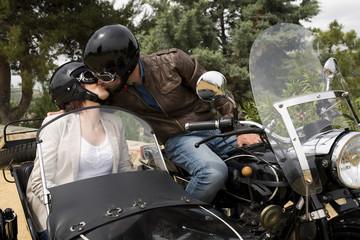 Couple kiss in custom chopper sidecar bike