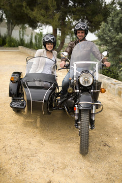 Couple at sidecar bike  posing with helmet at park