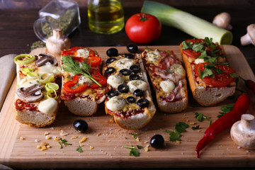 Different sandwiches with vegetables and cheese on cutting board on table close up