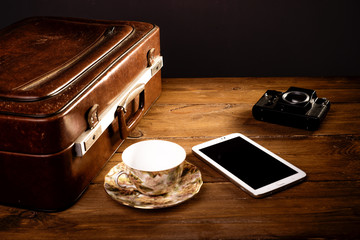 Suitcase and old camera, tablet, phone and a cup of coffee