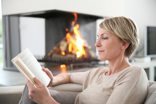 Middle-aged woman reading book by fireplace