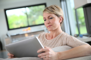 Woman websurfing with digital tablet at home