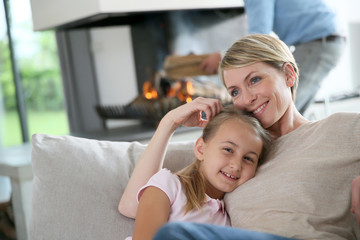 Mother and daughter relaxing by fireplace, laying in couch
