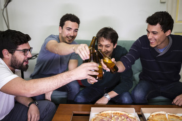 friends with pizza and bottles of drinks at apartment student