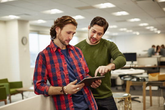 Two men looking at a digital tablet screen.