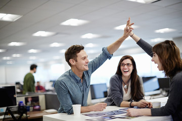 Three people in office looking at photographs and giving high five