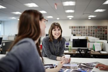 Two women talking at desk in office
