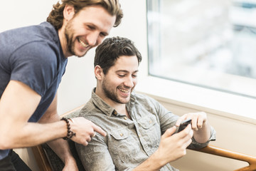 Happy businessmen using smartphone in office