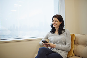 A businesswoman seated by a window, holding a smart phone.