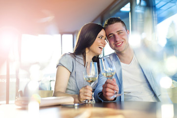 Beautiful young couple drinking wine in a bar