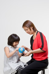 Little Asian woman teaching by the globe to the student
