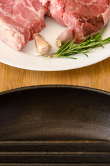 Raw steak with rosemary and garlic near cast-iron frying pan